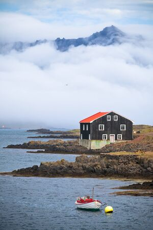 Lonely Black Wooden House at coastline�in East Iceland. Vertical shot Stock Photo - 16558928