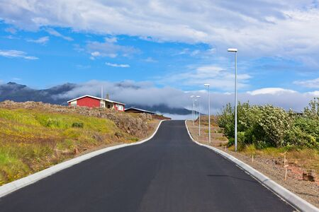 Red Small House and new asphalt road in East Iceland. Horizontal shot Stock Photo - 16584890