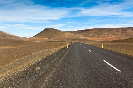 Highway through dry gravel lava field landscape under a blue summer sky. Highlands of Central Iceland. Stock Photo - 16595759