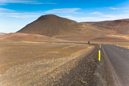 Highway through dry gravel lava field landscape under a blue summer sky. Highlands of Central Iceland. Stock Photo