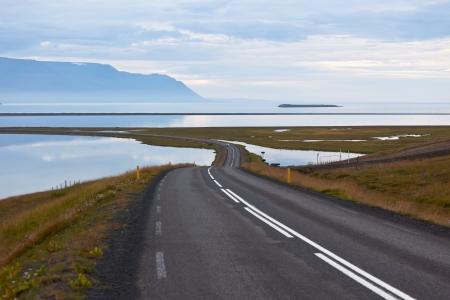 Curve Road through sea lagoon at twilight at North Iceland. Stock Photo
