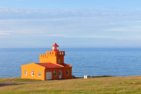 North Iceland Sea Landscape with Orange Lighthouse and Blue Sky photo