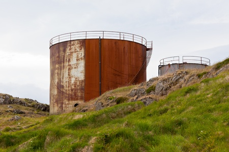 Rusted above ground storage tanks at dull day photo