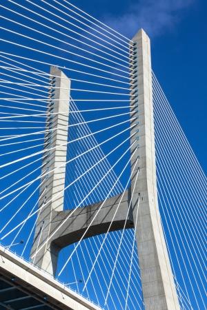 Modern bridge fragment: white cables against bright blue sky