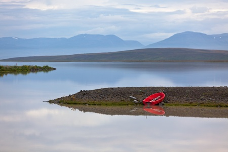 Iceland Evening Water Landscape with Red Boat and Reflection in the Water photo