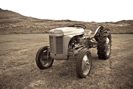 Retro Tractor on the Iceland field. Sepia toned image photo