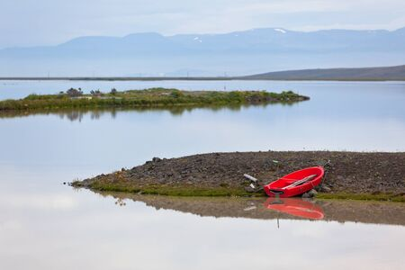 Iceland Landscape with Red Boat and Reflection in the Water photo