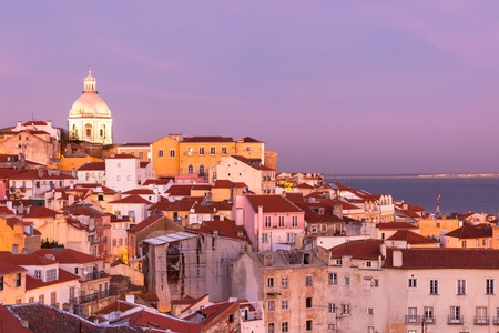 violet residential: Panorama of old traditional city of Lisbon with red roofs and view of river Tagus at sunset