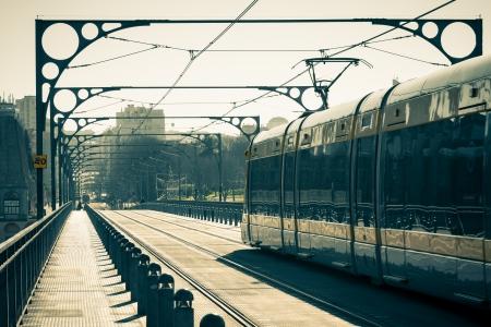 The Porto Metro Train crosses the Dom Luis 1 Bridge over the River Douro at Sunny Day  Toned image Stock Photo - 18231701