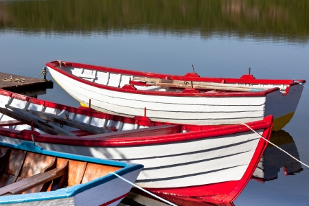Floating Bright Wooden Boats with Paddles and Its Reflection in a Water photo