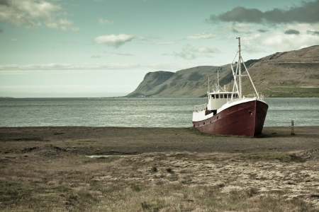 An old fishing vessel that shipwrecked on the northern coast of Iceland in the Westfjords region  Filtered image photo