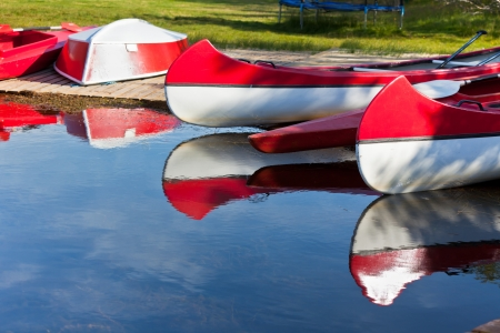 Red and White Canoes and Boats with Paddles and Its Reflection in a Water photo
