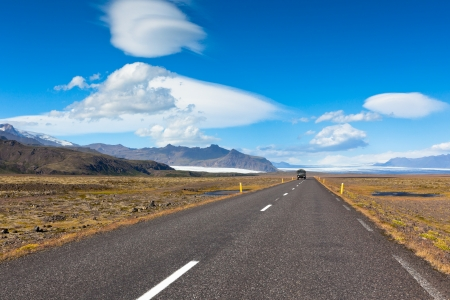Highway through South Icelandic landscape under a blue summer sky with clouds