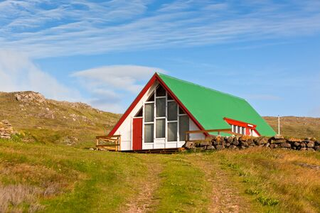 Bright Siding House with Green Roof in Iceland  Sunlight and Blue Sky