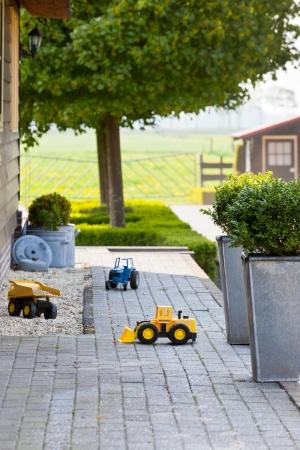 Ghild Toy Cars at Suburban House Back Yard. Vertical shot photo