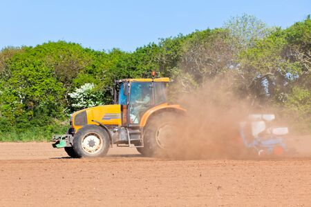 Agriculture - Tractor with plowes on the spring field photo