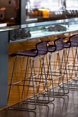 Empty row of stools at a close bar. Vertical shot