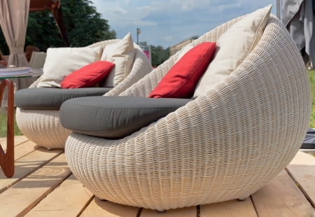 Soft wicker armchairs with color pillows outdoors. Horizontal shot photo