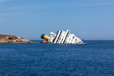 GIGLIO, ITALY - APRIL 28, 2012: Costa Concordia Cruise Ship at Italian Giglio Island Coastline after Shipwreck at January, 13, 2012. The ship, carrying 4,252 people from all over the world.