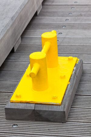 cleat: Closeup of Bright Yellow Boat Cleat on a dock pier. Vertical shot Stock Photo