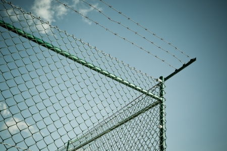 enclosures: A chain link fence, topped by razor wire. Horizontal shot Stock Photo