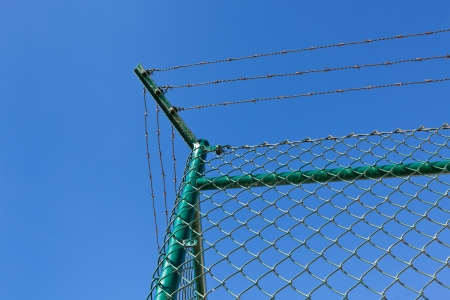 A chain link fence, topped by razor wire at bright blue sky background. Horizontal shot  photo