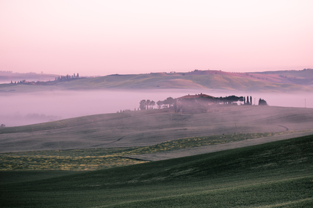 Morning fog view on farmhouse at Valley d Orcia in Tuscany, Italy photo