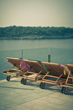 Hotel Poolside Chairs with Sea view  Vertical vintage style shot photo