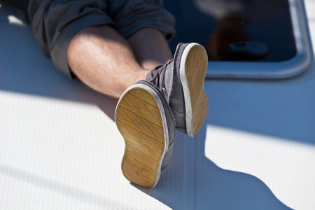 hairy legs: A pair of hairy man legs in pants and topsiders on white yacht deck  Yachting