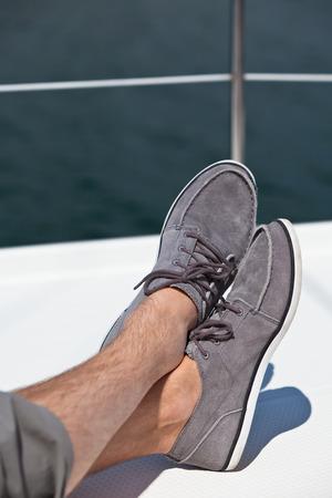 piernas hombre: Un par de hombre peludas piernas en pantalones y topsiders en el yate blanco cubierta Yachting Foto de archivo