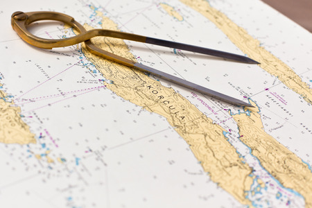 Pair of compasses for navigation on a sea map with low depth of field Stock Photo