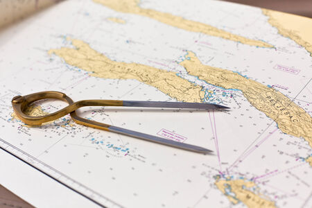 charting: Pair of compasses for navigation on a sea map with low depth of field Stock Photo