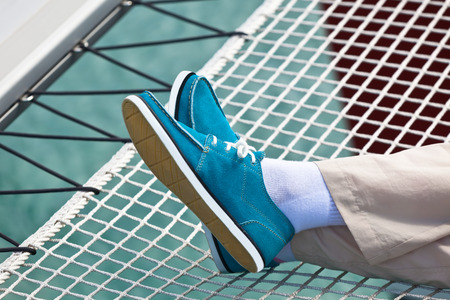 A pair of human legs in pants and bright blue topsiders on yacht hammock background  Yachting photo