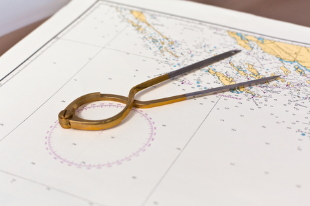 Pair of compasses for navigation on a sea map with low depth of field photo