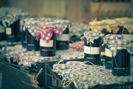 Many preserving jars with dark jam in a market. Horizontal shot photo
