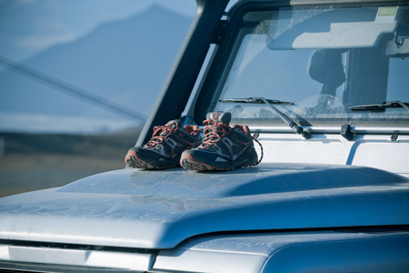 4wd: Trekking shoes are drying on a dirty 4wd car bonnet. Adventure mood