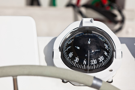 Sailing yacht compass and control wheel. Horizontal close up shot photo