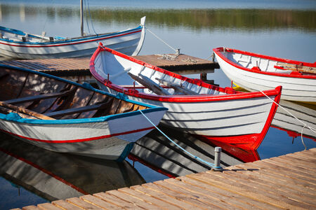 Floating Color Wooden Boats with Paddles in a Lake photo