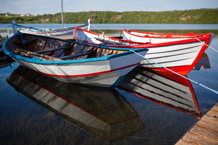 Floating Color Wooden Boats with Paddles in a Lake. Horizontal shot photo