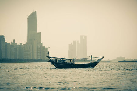 abu dhabi: Abu Dhabi buildings skyline with old fishing boat on the front
