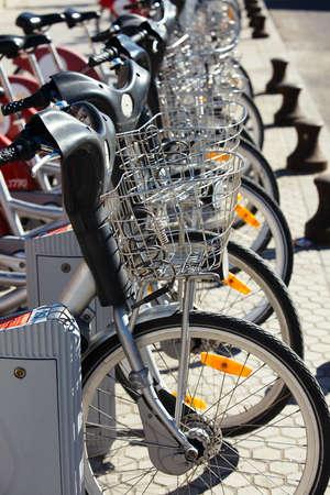 cicla: Bicicletas de alquiler ciudad estacionados en fila. Pequeño GRIP, el foco está en el centro de la imagen