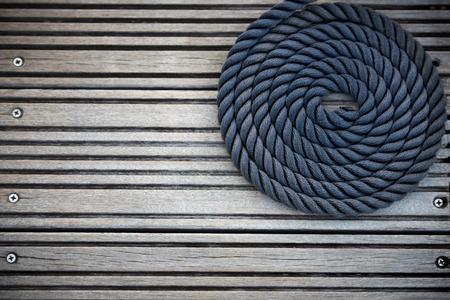 A curled mooring rope on a wooden pier. Copy space Stock Photo