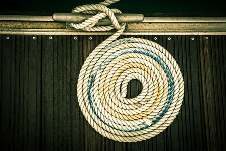 A mooring rope with a knotted end tied around a cleat on a wooden pier photo