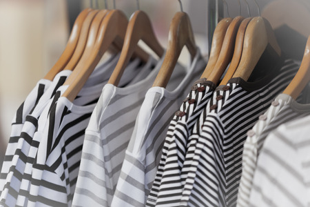 ropa colgada: Rayado Jerseys femeninas en una tienda de ropa. Portarretrato disparó con pequeño GRIP