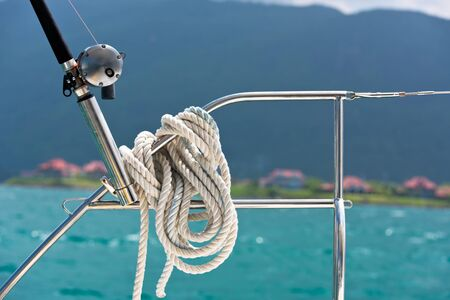 hand rails: A rope tied around a lifeline and a fishing rod on a yacht. Ocean background