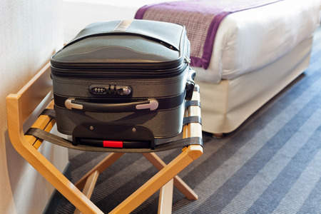 Hotel room with a suitcase on the luggage place and the bed