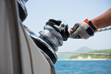 hand crank: Winch and sailors hands on a sailboat. Shot with a selective focus