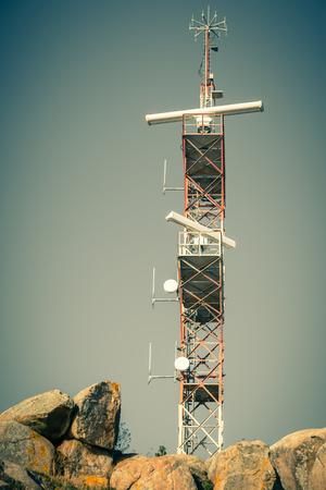 communication tower: A navigation communication tower against a blue sky. Filtered shot