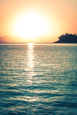 sea water: Beautiful tropical sunset ocean background. Vertical filtered shot