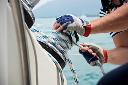 marinero: Cabrestante y marineros manos en un velero. Disparo con un enfoque selectivo Foto de archivo